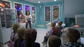 A biologia da escola primária, jovem mulher que descreve a anatomia humana perto do esqueleto com grupo de crianças, texto aparec video estoque