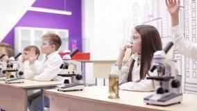 Biologia della scuola elementare, classe di chimica - bambini che guardano tramite il microscopio video d archivio