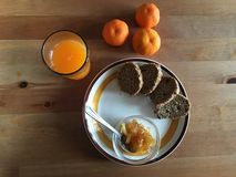 Biologiacal breakfast with jam brown bread fresh mandarin juice Royalty Free Stock Photo