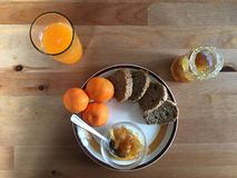 Biologiacal breakfast with jam brown bread fresh mandarin juice Royalty Free Stock Photos