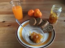 Biologiacal breakfast with jam brown bread fresh mandarin juice. Biologiacal breakfast with jam brown bread on wood table for an healthy life all handmade Royalty Free Stock Photos