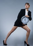 Biological clock concept. Beautiful woman on backgound holding a clock royalty free stock photo
