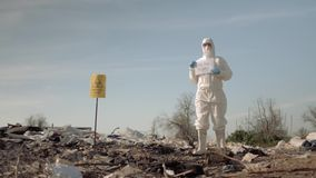 Biological danger, hazmat man into protective clothing shows sign save the planet on rubbish dump with pointer stock video footage