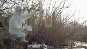 Biological danger in nature, hazmat researcher into Protective Costume taking infected water sample in test tubes for. Biological danger in nature, hazmat stock video