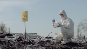 Biological hazard, woman scientist ecologist in uniform and protective gloves taking sample of the garbage from big stock footage