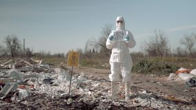 Biological hazard, young woman in uniform and protective glasses holding poster think green standing at trash dump in stock video