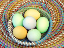 Biological organic blue green yellow turquoise easter eggs in a colourful basket on a wooden table stock photos