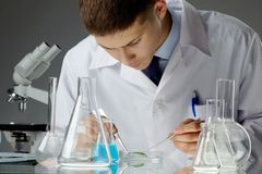 Biological specimen. Young scientist studying a bio specimen in a Petri dish Stock Images
