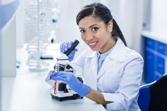 Delighted positive woman holding a microscope. Biological studies. Delighted positive nice woman holding a microscope and smiling while doing biological research Stock Images