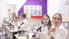 Biologie d'école primaire, classe de chimie enfants regardant par le microscope banque de vidéos