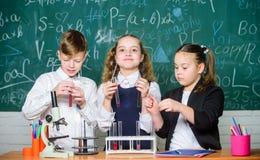 Biologii wyposa?enie ucznie robi biologii eksperymentuj? z mikroskopem w lab Ma?e dzieci uczy si? chemi? wewn?trz fotografia royalty free