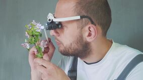 Biologist or agronomist with special glasses, is making an analysis of apple bloom.