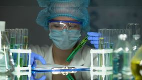 Biologist analyzing plant in green preservative agent writing experiment results