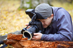 Biologist in the field. Biologist photographing small details with professional equipmant in the forest in autumn Stock Photos
