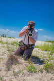 Biologist in the field. Biologist photographing plants in the sand dunes of Vadu beach, Romania Royalty Free Stock Image