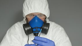Biologist in a protective suit, mask. wearing glasses and gloves, he dials a vaccine from an ampoule into a syringe