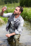 Biologist take a sample in a river in order to do some test Stock Photos