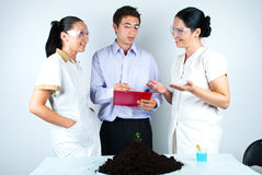 Biologist team having discussion in laboratory. Three biologists having a conversation and planning  in laboratory,man taking notes and one of his colleague Royalty Free Stock Images