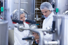 Biologist team talking and wearing hairnet. In the factory Stock Photo