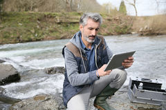 Biologist testing water quality of river. Biologist testing quality of natural water Stock Image