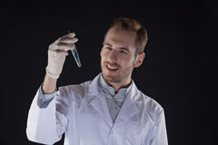 Biologist with a vial smiles. Biologist in the white coat is holding a vial and smiling Royalty Free Stock Photography
