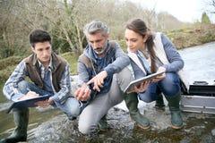 Biologo con gli studenti di biologia che provano l'acqua di fiume Immagini Stock Libere da Diritti