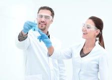 Biologo di due un riuscito scienziati che esamina la boccetta con il liquido fotografia stock