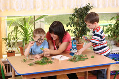 Biology lesson. In preschool - teacher and two boys stock photos
