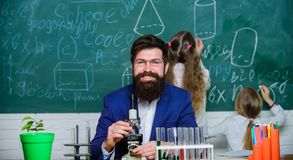 Biology plays role in understanding of complex forms of life. School teacher of biology. Man bearded teacher work with. Microscope and test tubes in biology royalty free stock image