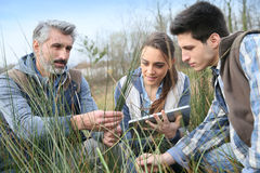 Biology professor with students outdoors stock image