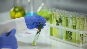 Bioloog die buis met installatie in behoudsvloeistof merken, invloed op aard stock videobeelden