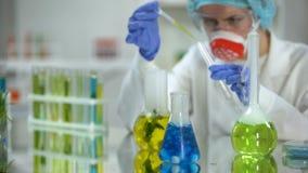 Bioloog die gele organische vloeibare steekproef voor analyse, de kosmetiekuittreksel nemen stock footage