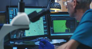 Bioloog die steekproef met microscoop analyseren stock videobeelden