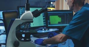 Bioloog die steekproef met microscoop analyseren stock video