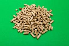 Biomasa de las pelotillas Pelotillas de madera en un fondo verde, espacio de la copia imágenes de archivo libres de regalías