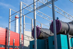 Biomass boilers. Wood chips boilers of the modern biomass co-generation plant on the blue sky background while construction process stock photo