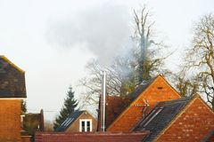 Biomass fuel boiler. Buckingham, UK - December 11, 2018. A domestic biomass flue pipe emits smoke and pollution into the environment stock photos