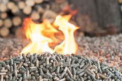 Biomass of wooden material in flames. Different kind wooden pellets in fire - renewable energy, biomass stock photos
