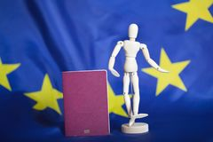 Biometric passport and dummy figurine in front go EU flag. Biometric passportand dummy figurine in front go EU flag. Closeup stock images