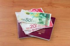 Biometric passports with Israeli new shekel banknotes royalty free stock images