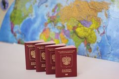 Biometric russian passports are in a row on the background of the world map. . The passport of the Russian Federation. The concept of tourism and travel stock photo