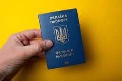 Biometric Ukrainian passport in hand on a yellow background stock photo