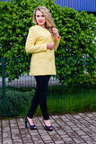 Bionda attraente in cappotto giallo che posa emozionalmente al parco Immagini Stock