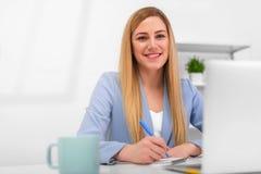 Bionda attraente in un vestito blu in un ufficio luminoso che lavora ad un computer portatile Fotografia Stock