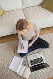 Bionda che fa compito e che si siede sul pavimento facendo uso del computer portatile Immagini Stock