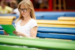 Bionda con il libro di lettura di vetro fra i banchi Immagini Stock
