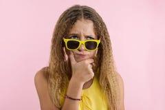Bionda dell'adolescente con capelli ricci che aggrotta le sopracciglia, aggrottante le sopracciglia il suo sopracciglio mentre di Immagini Stock Libere da Diritti