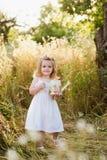 Bionda della bambina in un vestito bianco in giardino con acqua, ridente, infanzia, rilassamento, serenità Fotografia Stock Libera da Diritti