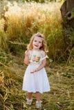 Bionda della bambina in un vestito bianco in giardino con acqua, ridente, infanzia, rilassamento, serenità Fotografie Stock Libere da Diritti