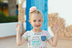 Bionda della ragazza 5 anni che gesturing e che sorridono su un fondo di blu Immagine Stock